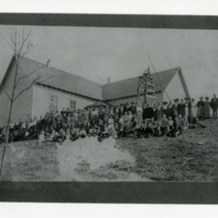 Group of Children and Adults in Front of Schoolhouse